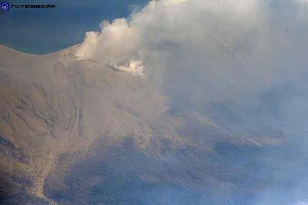 写真左下の黄白色の堆積物が埋めている谷が向江浜方面へ続く谷。2014年8月3日の噴火時に火口の形状が広がったと考えられている西側割れ目付近から小さな噴気が数多く出ているのが見える。西側斜面の樹林の上を箒ではいたように複数方向へ噴出物が分布しているようすが見える。(新岳の北西方向より撮影)(2015年5月29日撮影)