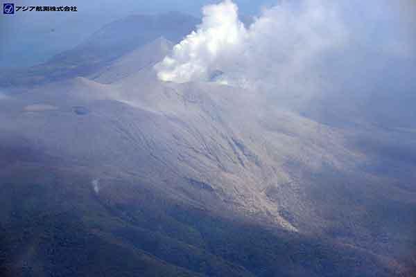 新岳山頂火口の北側斜面と新岳の北側に位置する山体との鞍部には火砕流堆積物が厚く分布し、平滑な斜面となっている。この火砕流堆積物の表面からは、水蒸気もしくは砂埃が立ちのぼっている。新岳北側山体の北~北西斜面には樹木の下部に火砕流堆積物が確認できるが、目立った倒木は見られない。写真手前側の斜面上には白色の煙状のものが確認できるが、原因等の詳細は不明である。(新岳の北方向より撮影)(2015年5月29日撮影)