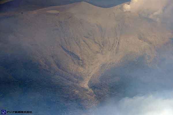 新岳の北西に伸びる谷に沿って火砕流堆積物が分布しているが、傾斜が緩くなっている標高350m付近から標高180m付近までは、特に厚く堆積している(写真番号2の拡大写真)。標高180m付近より低標高部では、斜面が階段状になっている部分に火砕流堆積物が確認できる。(新岳の北西方向より撮影)(2015年5月29日撮影)