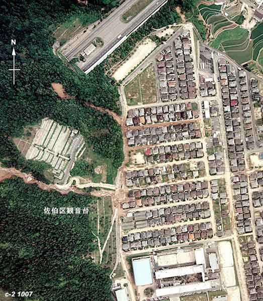 佐伯区東観音台団地:中央部に大規模な宅地造成地があり、西側から流れ込む渓流で土石流が発生し、ダムを乗り越えるようにして、住宅地に土砂が流入した。(1999年7月1日撮影)