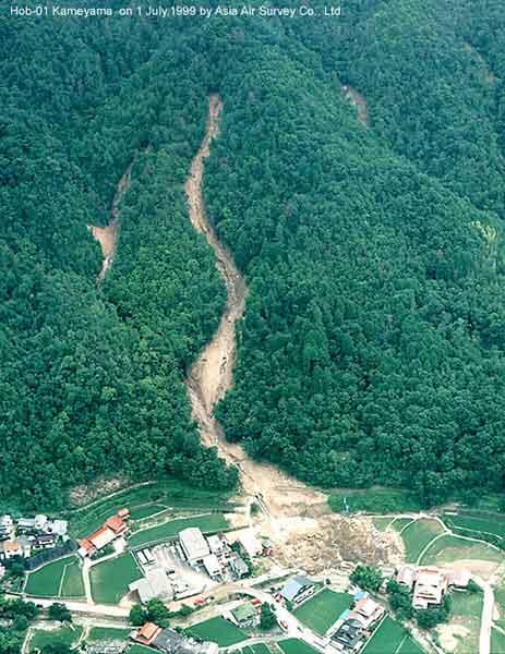 安佐北区亀山9丁目の土石流:谷の源頭部の崩壊によって発生した土石流は、狭い谷を高速でかけ下り、谷の出口で斜め方向に飛び出し民家を直撃した。この付近には比較的硬質の細粒花崗岩が分布する。マサ化の程度は低く、斜面には崖錐(過去の土石流堆積物)が多く分布する。(1999年7月1日撮影)
