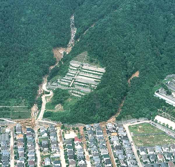 佐伯区東観音台団地:土石流は、写真の範囲外の、尾根の直下でも発生している。写真上では2基のダムと沈砂池が見られる。土石流は、沈砂池でほぼ停止したが、あふれたものは団地内の道路を流下した。急斜面上に見える雛壇は墓地。(1999年7月1日撮影)