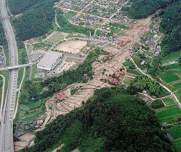 安佐北区譲羽(ゆずりは)団地:写真の左に見えるのは中国道。広島北JCTのすぐ北東に位置する。画面中央を右から左へ流れる渓流を土石流が通過、一部が氾濫し住宅が破壊された。(1999年7月1日撮影)