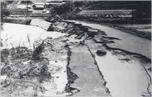 奥畑川の増水で護岸が流失、道路が半分削り取られた(洲本市国出付近):兵庫県南西部と淡路島で200~300mmの雨が降り、家島町では6日22時から7日2時までの4時間に196mm、津名郡一宮町の郡家では7日1時から4時までの3時間に190mmの記録的な集中豪雨があった。これらの地域では、6月末からの連日の降雨で地盤がゆるみ、河川が増水しているところにこの豪雨が降ったため、大きな水害が発生した。