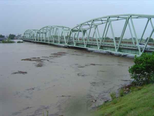 平成16年7月新潟・福島豪雨 小須戸橋付近:2004(平成16)年7月12日の夜から13日の夕方にかけて、信濃川下流の山間部を中心に400㎜を超す大雨が降りました。この大雨により、いっきに水が五十嵐川や刈谷田川に流れ、堤防が壊れ、三条市、見附市、長岡市(旧中之島町)が大きな被害を受けました。この洪水を受け、「河川災害復旧等関連緊急事業(復緊事業)」を行い、平成21年度までの5カ年間で堤防の嵩上げ等の整備を集中的に実施しました。死者15名、全半壊家屋979戸、浸水家屋17,071戸(床上10,712戸、床下6,359戸)。