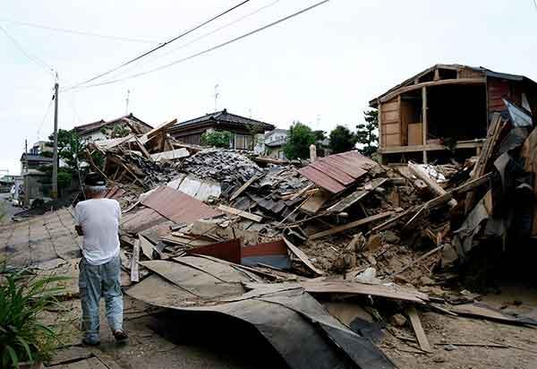 新潟県柏崎市で16日、地震で倒壊した家屋のわきを通り過ぎる男性。日本のメディアと当局者によると、新潟県中越地方を襲った震度6強の地震で少なくとも4人が死亡し、400人以上が負傷した。柏崎刈羽原発では火災が起きた。