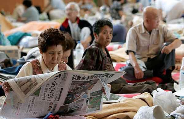 新潟県柏崎市で17日、避難所の体育館で新聞を読む女性。新潟県中越地方を襲った震度6強の地震で数百棟の住宅が倒壊。少なくとも7人が死亡した。避難所では8000人近くが不安な夜を過ごした。被災地では2日間降雨の予報で、地滑りが被害を広げる恐れがある。