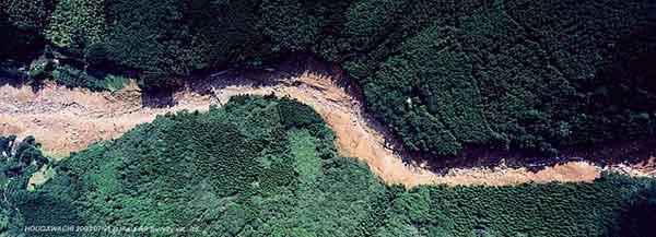 流下経路垂直写真:通過部分。渓流の曲線区間で、土石流の一部が斜面に乗り上げていることがわかる。治山ダムが確認できる。右が北、左が下流。(2003年7月21日撮影)
