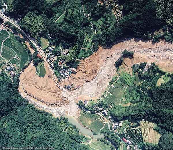宝川内集地区垂直写真:茶色の部分が土石流の通過および氾濫堆積域。灰色の部分は、土石流堆積後に2次侵食を受けた部分。右が北。(2003年7月21日撮影)