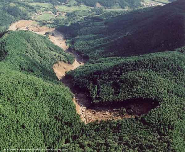宝川内土石流斜め写真(北):北側の崩壊地上空からの俯瞰画像。遠くに見えるのが、集地区。(2003年7月21日撮影)