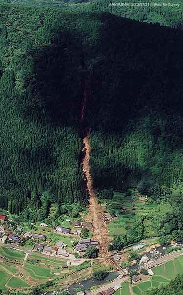 深川地区新屋敷土石流斜め写真:ちょうど雲の影の部分に崩壊がある。土石流が直線状に河川まで流れたことがわかる。東方向を俯瞰するように撮影したもの。(2003年7月21日撮影)
