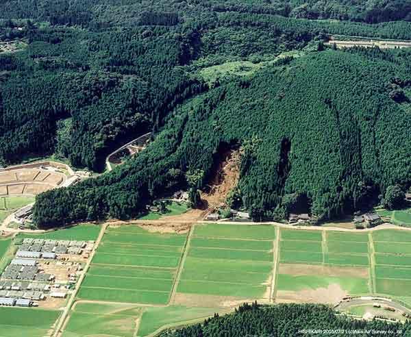 菱刈土砂崩壊斜め写真:崩壊地は斜面の中腹に位置する。崩壊土砂は薄く広がり、水田に達している。北に向かって撮影、右が東方向。(2003年7月21日撮影)