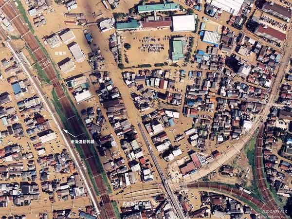 西枇杷島駅と新幹線 名鉄名古屋本線西枇杷島駅の、対面島式ホームが水面に浮かんでいるように見える。中央上部にある西枇杷島小学校の校庭には、多数の自家用車が見え、避難場所であることがわかる。左側にあるのは、東海道線と東海道新幹線。ちょうど新幹線が通過している。(写真上が北方向)(2000年9月12-14日撮影)