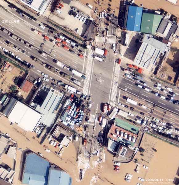 国道22号交差点における救援活動状況 西枇杷島町を北西から南東に横断する国道22号線は、かろうじて水面上にあり、県道との交差点(古城)が防災拠点となった。スロープを利用して、ゴムボートが救援に出発している。(写真上が北方向)(2000年9月12-14日撮影)