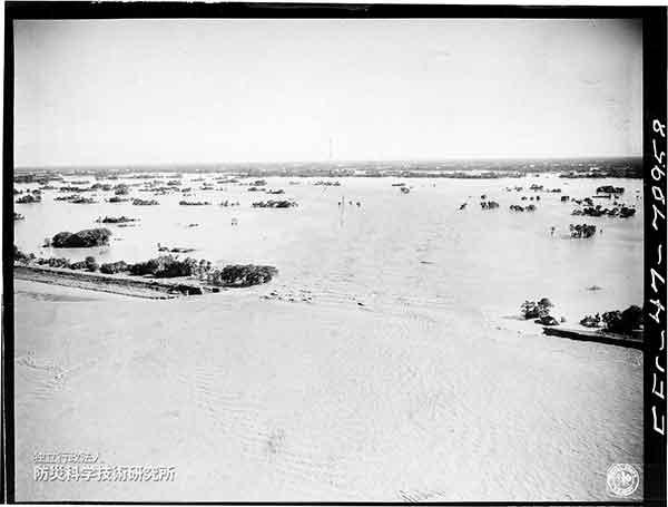 利根川新川通りの破堤口から平野部に向かって溢れ出る利根川の濁流。破堤口は約400m。浸水域に浮かんで見える島状の部分は自然堤防。
