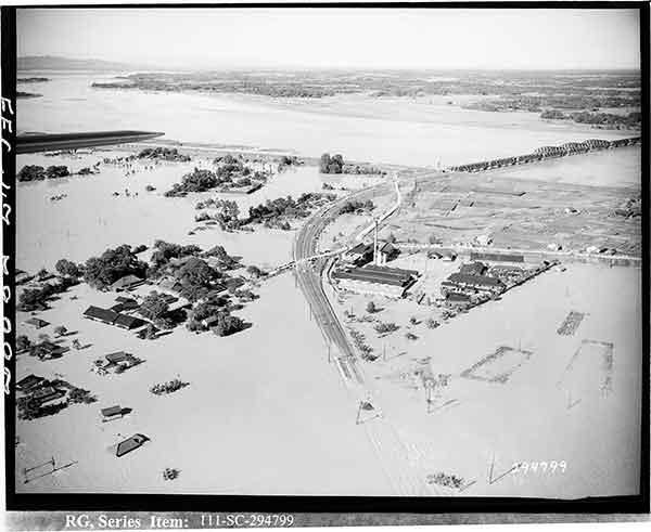 画面左上方に利根川・渡良瀬川合流点、右手に国鉄東北本線の利根川鉄橋が見える。鉄橋下流の右岸には、控え堤があったために浸水を免れた。
