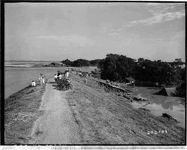 約400mに渡って崩れた破堤口付近に集まる人々。遠景に東武鉄道の利根川鉄橋が見え、川の上流から下流に向かって写している。画面左の利根川から破堤口へ向う流れはかつての利根川の本流だった。