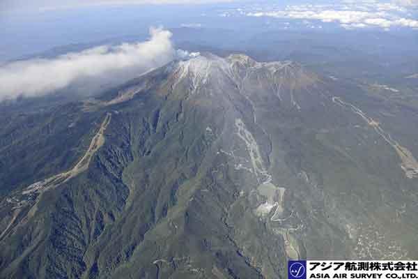 【2014/9/28 9:48撮影】東側斜面。火口から開田高原(写真右下)方向では火山灰が堆積して白くなっている。写真中央は御岳ロープウェイスキー場。噴煙は南~南東方向に延びている。(東方向より撮影)(2014年9月28日撮影)
