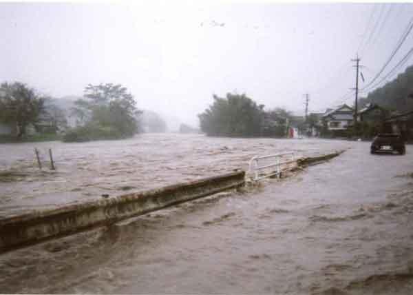 賀来地区無堤部の越水状況(平成16年10月洪水):10月13日9時にマリアナ諸島近海で発生した台風23号は、18日9時に超大型で強い勢力となって20日13時頃、大型の強い勢力で高知県土佐清水市付近に上陸した後、18時前、大阪府泉佐野市付近に再上陸した。18日から20日までの総雨量は大分で409mmを記録しました。大分県内での災害規模は死者・行方不明者1名(不明)、浸水被害1,082戸(242戸)。ただし( )は大分川流域内