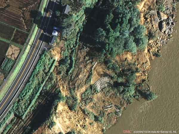 川口町大字相川付近:信濃川沿いの斜面に発生した崩壊によりJR上越線の路盤が流失した。線路が宙吊りになっているのが判読できる。(2004年10月24日撮影)