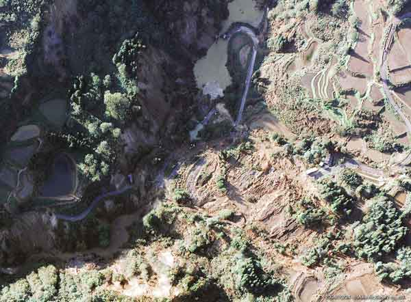 山古志村寺野地区:地すべり崩壊によって川が堰き止められて、小規模な天然ダムが形成されている。水面にはさまざまな浮遊物がみられる。写真上方が上流側。(2004年10月24日撮影)