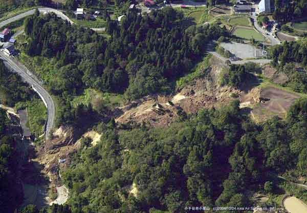 小千谷市小栗山地すべり性崩壊:崩壊によりため池が決壊し、水が完全に失われている。流下した土砂が住宅と道路に流れ込んでいる。(2004年10月24日撮影)