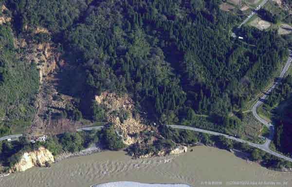 小千谷市川井信濃川本流沿い崩壊:信濃川に沿う道路沿いの斜面で崩壊が発生、道路ごと川にすべり落ちている。(2004年10月24日撮影)