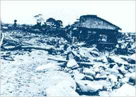 土石流による巨石・流木の堆積状況(神戸市灘区篠原本町・都賀川):【被害の状況】梅雨前線の降雨により六甲山系の南斜面では多数の土石流が発生しました。【土石流の状況】この災害では、500万立方メートルを上回る土砂が市街地に押し寄せ、河川を氾濫させ、住宅地を埋めました。