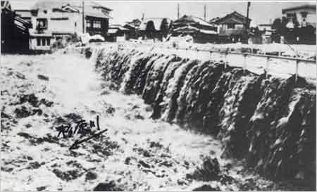 杉原川に架かる市道山手高田井線豊川橋越水状況(西脇市山手町付近):2日から5日にかけて台風が本邦南岸沖を北東に進み、これが梅雨前線を刺激したため前線活動が活発化して、2~4日にかけて大雨を降らせた。県内では、3日夕刻から降り出した雨は、4日の8時から11時にかけて県南部地方の氷上・多可・神崎郡、西宮市一帯に1時間雨量40mmを超える局地的豪雨となった。これにより、加古川、市川、夢前川の中・上流で氾濫し、死者3名、家屋の全壊・流失23戸など、大きな被害が発生した。