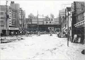 宇治川は暗渠河川のため土砂で閉塞され濁流は路上を流れ出した。写真中央の高架は阪急電鉄三宮駅付近(神戸市中央区元町付近):昭和42年7月豪雨は、九州北部から関東地方にかけての広範囲に大雨を降らせ、全国で死者365名、建物の全半壊2,266棟、浸水家屋約30万棟を超える被害を出した。この豪雨の引き金となった台風第7号くずれの温帯低気圧は、8日に沖縄付近で弱い熱帯低気圧に衰え、更に9日に五島列島付近で温帯低気圧になった。この頃、日本の南岸に停滞していた梅雨前線に、熱帯低気圧が運んできた高温多湿の気流が送り込まれ、また、北側からは寒冷な気流が送り込まれたため、前線が激しく活発化した。更に、台風くずれの低気圧が前線上を猛スピードで山陽、近畿および中部地方と縦断、抜き打ち的に佐世保、伊万里、呉、神戸等に300mm以上の集中豪雨を降らせて、10日未明に関東地方から鹿島灘に抜けた。神戸市では9日8時頃から断続的に雨が強まり、16時から18時までの2時間に127.3mmの強い雨が降り、更に20時から21時までの1時間に59mmの強い雨が降った。このため、夕方頃から夜にかけて六甲山系から市内に鉄砲水が発生し、所によっては50~100cmの濁流が渦を巻いて市街地を襲った。六甲山系の山沿いの宅地造成地では山崩れが相次いで起こり、家屋の流失、倒壊などで生き埋めによる犠牲者は100名にのぼった。