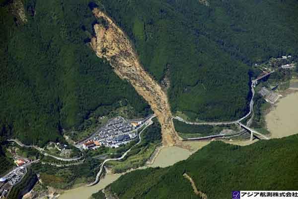 奈良県川上村迫地区:吉野川左岸山腹斜面より崩壊が発生し、大量の土砂流木とともに本川へ到達した。国道169号を横断するように土砂が流下し、国道が分断されている。 (2011年9月7日10時撮影)