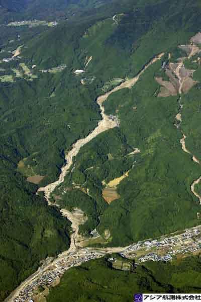 和歌山県那智勝浦町井関地区:那智川右支川上流で発生した崩壊が、土石流となって井関地区に到達した。支川沿いに県道43号があるが大量の土砂で埋没し、本川付近にも土砂が堆積している。(2011年9月7日8時30分撮影)