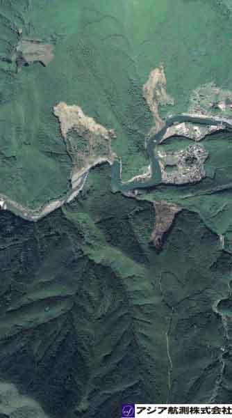 奈良県天川村九尾ダム上流坪内地区:左右岸の複数個所で斜面崩壊が発生。特に中央に見える崩壊は面積が広く、崩壊深が深い。崩壊土砂は天ノ川本川の河道に堆積し、湛水が見られる。現状では越流しており完全には河道は閉塞していない。(2011年9月7日撮影)