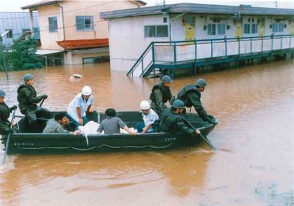 ボートで救助される住民(福島市):昭和61年8月1日にフィリピンのルソン島の東で発生した台風10号は、進路を北東に取り、4日朝には本州の南海上に達しました。その後、伊豆半島石廊崎の南海上で温帯低気圧に変わったものの、台風時と変わらぬ強い雨と風を伴ってさらに北東に進み、房総半島を縦断して鹿島灘に抜け、6日朝には宮城県沖に達し次第に東北地方から遠ざかっていきました。福島県内に4日午前6時頃から降り始めた雨は午後4時頃から本降りとなり、午後6時には県内全域に大雨洪水警報、強風波浪注意報が発令されました。降雨量は、浜通り地方が一番多く、次いで中通り地方、会津地方の順になっており、もっとも多いところでは500mmを記録しました。それに伴い阿武隈川の水位は上昇の一途をたどり、堤内堤外の区別が判然としないほど一面濁流に覆われました。さらに、谷田川や逢瀬川では堤防が決壊、沿岸の住宅、田畑、道路などに深い爪痕を残しました。この記録的な豪雨による被害総額は、約867億3,400万円にのぼり驚異的な数字を示しました。