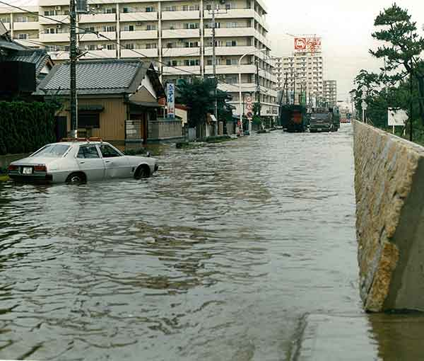 S61草加市 栄町の浸水状況:昭和61年8月の台風10号により、綾瀬川では8月5日最高水位3.86mを記録しました。この出水に対し、各排水機場による排水運転、水防団による土のう積み等の水防活動が実施されましたが、草加市や越谷市など各地で溢水氾濫が生じ、甚大な被害が発生されました。特に草加市では、昭和57年9月の台風18号に次いで災害救助法が適用されました。この洪水で綾瀬川では3度目となる河川激甚災害対策特別緊急事業が採択されました。