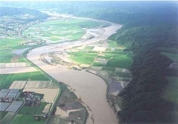 平取町市街地を下流から:<沙流川流域>平成15年8月洪水では、全川にわたって計画高水位を超過し、5,240m3/s(平取地点)の流量を観測し、死者3名、重傷者1名、家屋全壊10戸、半壊6戸、一部破損16戸、床上浸水79戸、床下浸水172戸の大きな被害を受けました。この洪水を契機に基本高水流量のピーク流量及び河川整備計画目標流量を変更しました。