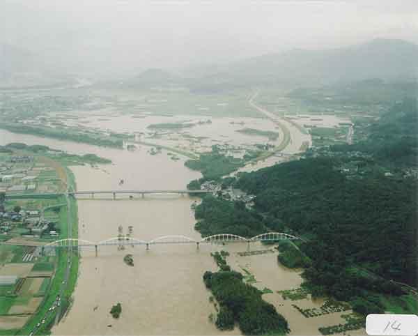 豊川からの氾濫水が県道を洗い洪水が堤内地へ浸水平成15年8月9日11:50頃(ほぼピーク時):台風10号は、7日には最も発達し、中心付近の気圧が945hPaと強い勢力を保ちながら8日21時30分頃には高知県室戸市付近に上陸した。台風の進行速度が比較的遅かったため、台風の強い雨域の影響を長時間受けることとなり、東海地方では8日から9日にかけて大雨となった。豊川・石田地点のピーク水位は、平成12年9月(東海豪雨)の水位を上回り、戦後最大洪水の昭和44年8月洪水にせまる水位となり、各地で浸水被害が発生するなど、甚大な被害をもたらした。