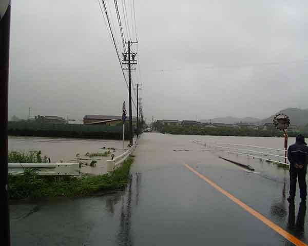 豊川からの氾濫水により交通が一時途絶えた県道 平成15年8月9日12:30頃(ほぼピーク時):台風10号は、7日には最も発達し、中心付近の気圧が945hPaと強い勢力を保ちながら8日21時30分頃には高知県室戸市付近に上陸した。台風の進行速度が比較的遅かったため、台風の強い雨域の影響を長時間受けることとなり、東海地方では8日から9日にかけて大雨となった。豊川・石田地点のピーク水位は、平成12年9月(東海豪雨)の水位を上回り、戦後最大洪水の昭和44年8月洪水にせまる水位となり、各地で浸水被害が発生するなど、甚大な被害をもたらした。