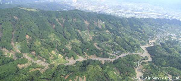 朝倉市杷木志波地区周辺(北川)。山腹斜面で多数の崩壊が発生し、多量の土砂が下流へと流出した様子がうかがえる。(2017年7月8日撮影)